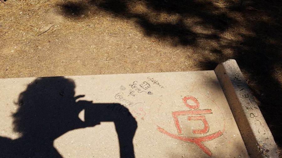 Capturing Shadow Taking Picture Graffiti Bench Shadow Sunlight Text Communication Outdoors Real People Cellphone Smartphone Human Hand Differing Abilities Copy Space Simple Expression Art Defacing Backgrounds Mix Yourself A Good Time Rewilding Second Acts