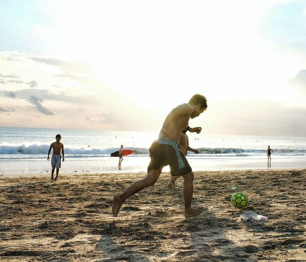Young Men Playing Soccer On Sand At Beach Against Sky During Sunset