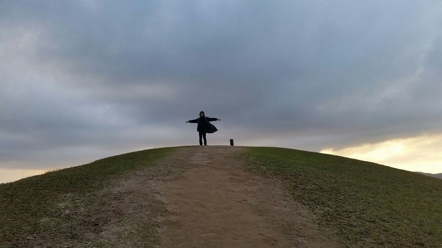 Low Angle View Of Man With Arms Outstretched Standing On Hill Against Cloudy Sky