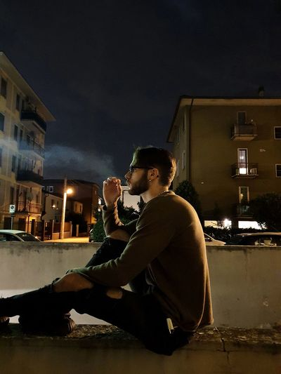 Boy smoking while sitting on street at night against sky