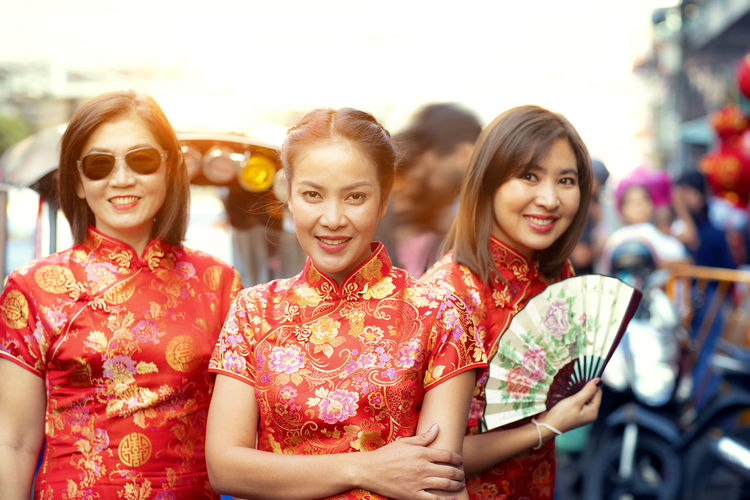 Portrait of women in traditional clothing holding hand fan standing outdoors