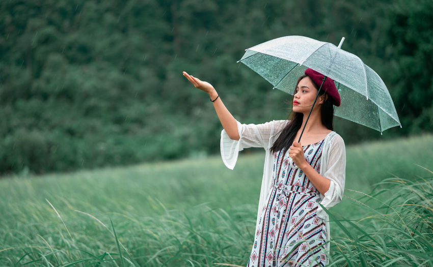 Woman holding umbrella while standing on field during rainy season
