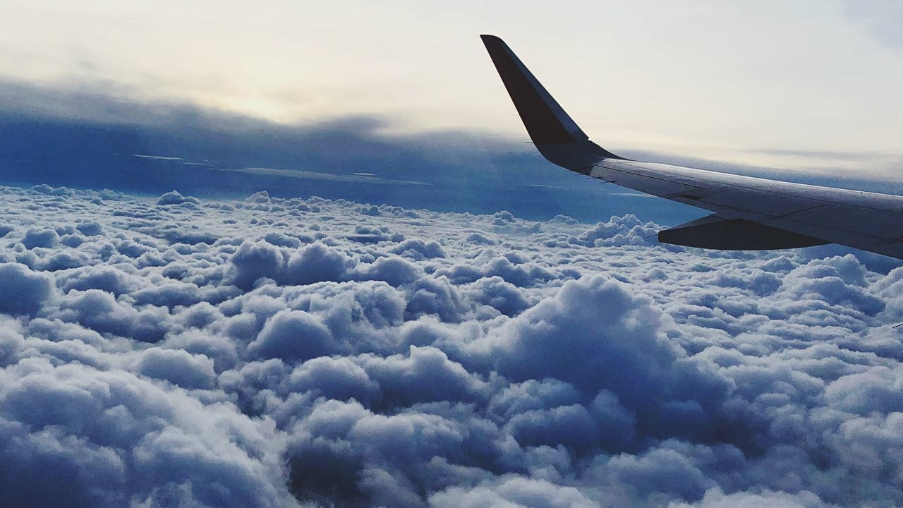 cloud - sky, airplane, air vehicle, transportation, mode of transportation, flying, sky, cloudscape, beauty in nature, aircraft wing, no people, scenics - nature, travel, nature, mid-air, outdoors, motion, journey, public transportation, day, softness, above, meteorology