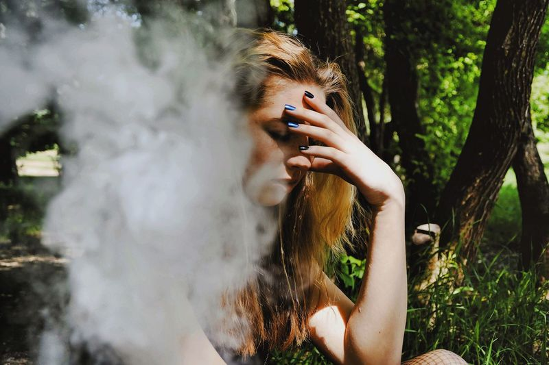 Close-Up Of Depressed Woman Sitting By Smoke In Forest