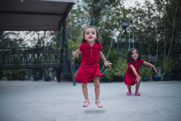 Twin Sisters Standing In Backyard