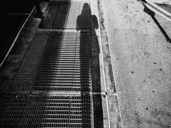 High angle view of shadow on metal grate