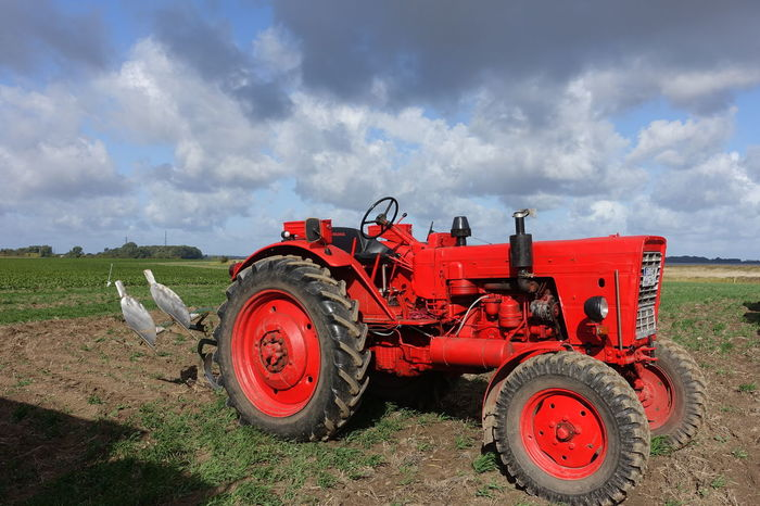Field Agricultural Equipment Agricultural Machinery Agriculture Cloud - Sky Day Field Land Land Vehicle Landscape Machinery Nature No People Outdoors Plow Red Tractor Rural Scene Sky Tractor Transportation