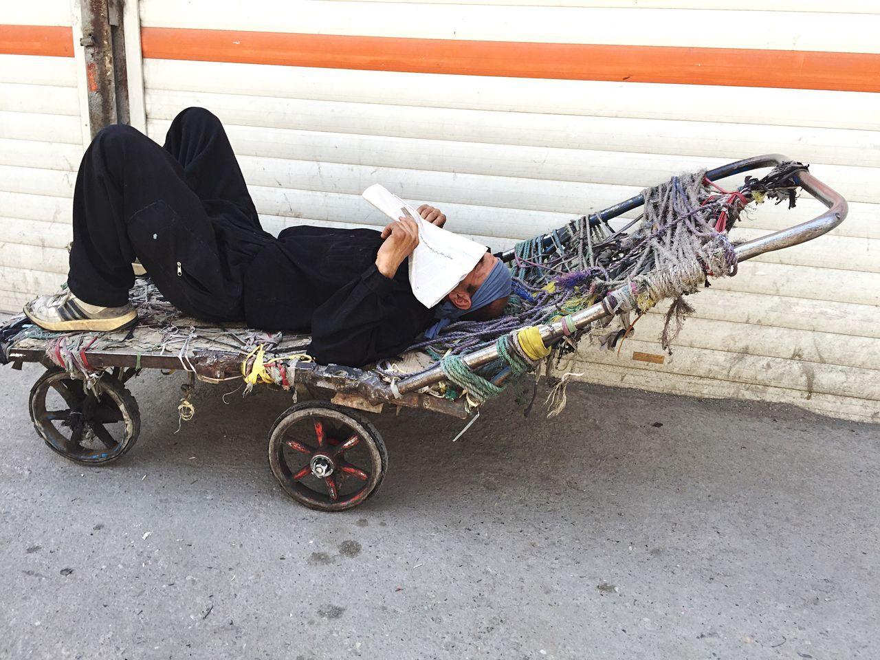 Man Sleeping On Cart Against Shutter At Molavi Square