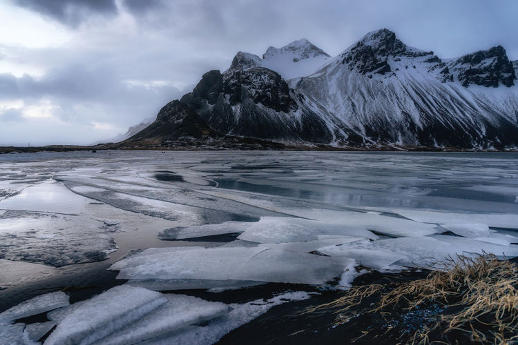 Frozen lake by mountains against cloudy sky