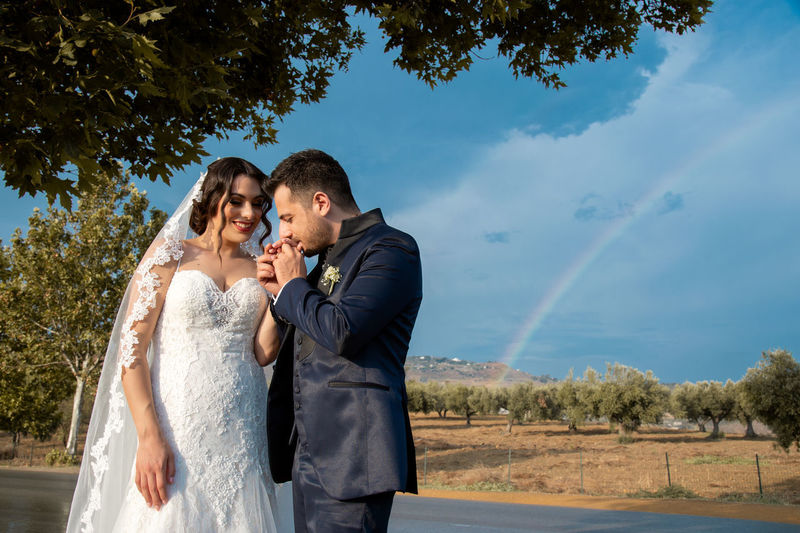 Adult Bonding Bridegroom Couple - Relationship Emotion Heterosexual Couple Love Men Outdoors Positive Emotion Real People Sky Standing Togetherness Tree Two People Women Young Adult Young Men Young Women