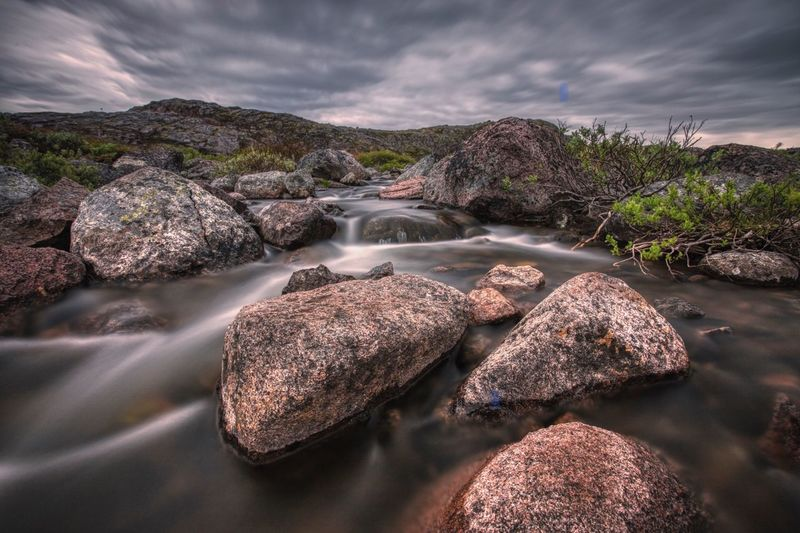 Rocks by river against sky