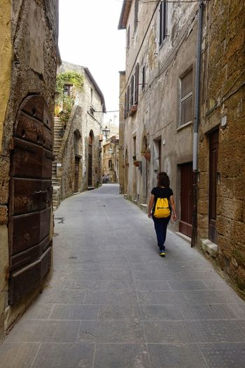 views of the medieval town of Pitigliano Architecture Built Structure Building Exterior Rear View Full Length Direction Real People The Way Forward Building One Person Lifestyles Walking Day City Women Footpath Leisure Activity Adult Casual Clothing Outdoors Alley Diminishing Perspective