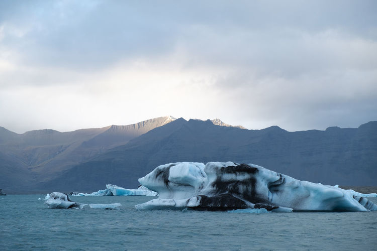 Scenic view of iceberg, sea and mountains against sky in the southern coast of iceland