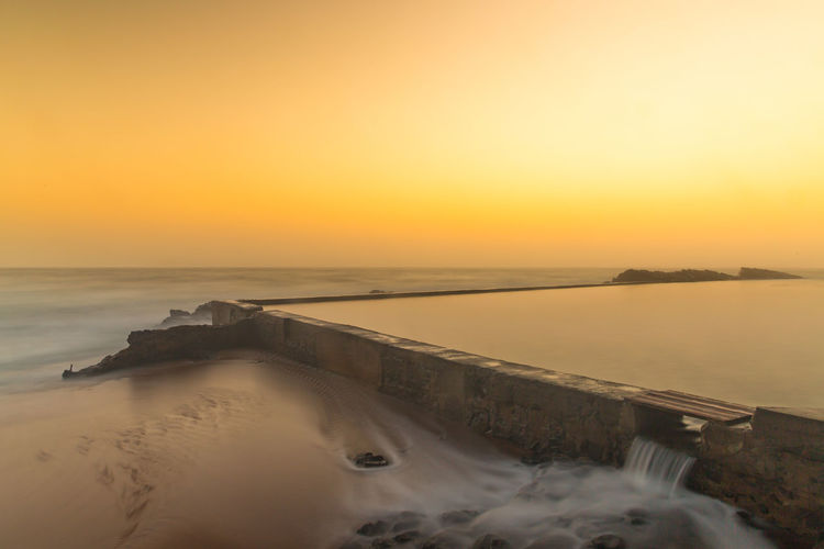 Infinity pool against sea and sky during sunrise