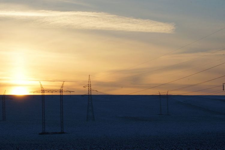 Electricity pylon on land against sky during sunset