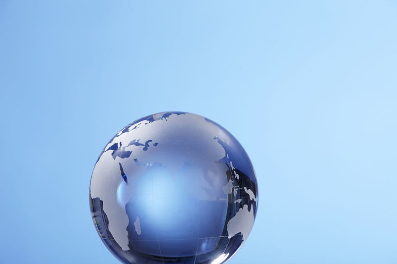 Close-up of globe against blue background
