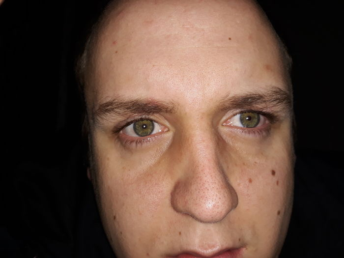 Close-up portrait of man over black background