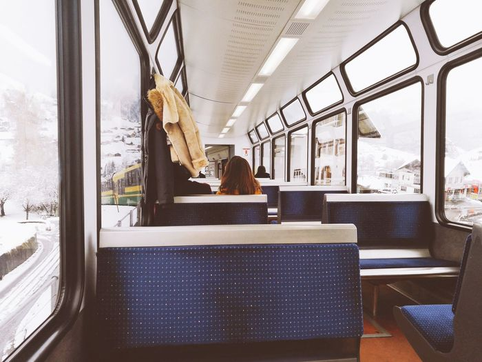 Rear view of woman sitting in train during winter