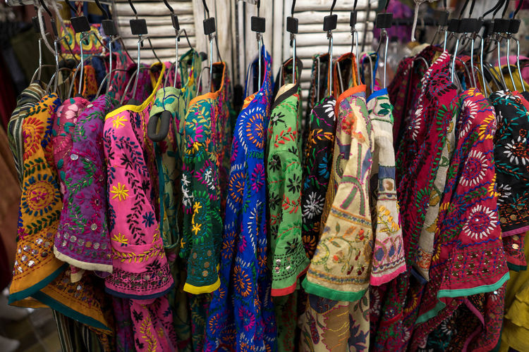 Multi colored clothes hanging in store for sale