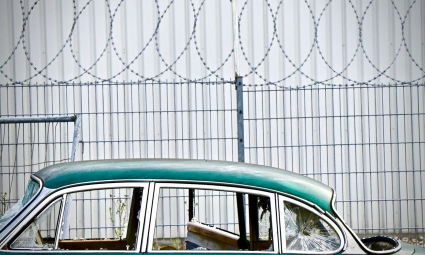 green damaged car Weathered Decayed Beauty Old Car Damaged Built Structure Architecture Car Day Mode Of Transportation Motor Vehicle No People Fence Boundary Wall - Building Feature Metal Glass - Material Pattern Building Exterior Barrier Nature Transportation Outdoors