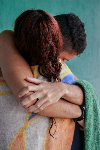 Couple embracing while wrapped in towel