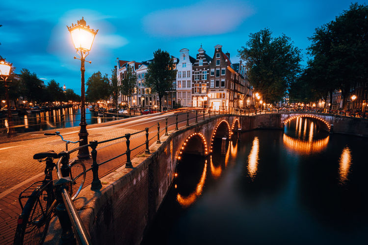 Night cityview of Famous Keizersgracht Emperor's canal in Amsterdam, tranquil scene with street lantern, illuminated bridge at twilight, Netherlands Architecture Built Structure Water Building Exterior City Illuminated Tree Street Light Sky Dusk Transportation Street River Bridge Nature Night Bridge - Man Made Structure Lighting Equipment Outdoors No People Arch Bridge Illustration Evening Amsterdam