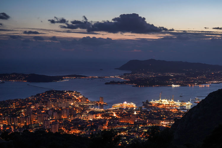 Aerial view of illuminated city by sea against sky