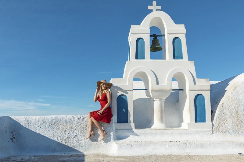 Woman sitting on church against blue sky