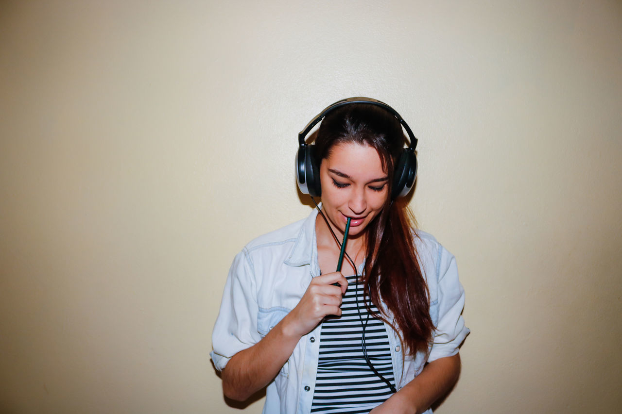 Young Woman Listening To Music Against Wall