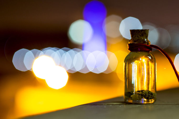 Close-Up Of Glass Bottle On Table Against Colorful Light