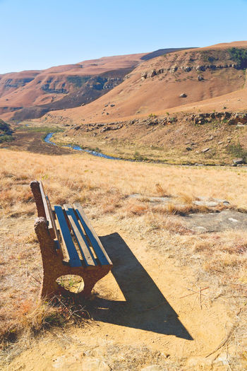 Empty bench on field by mountain against sky
