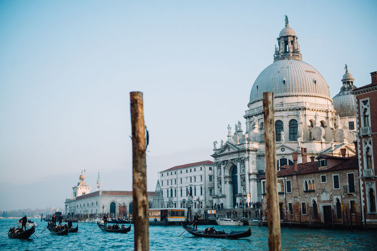 Gondolas in grand canal by san giorgio maggiore church against clear sky