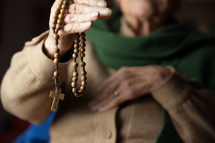 Midsection Of Senior Woman Holding Wooden Rosary Beads With Cross