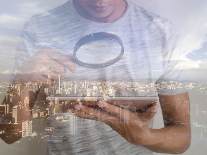 Reflection of man on glass window using digital tablet against cityscape
