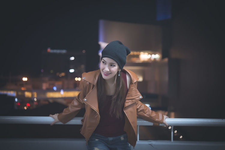 Smiling Young Woman Standing In Illuminated City At Night