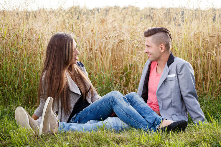 Young couple sitting on field