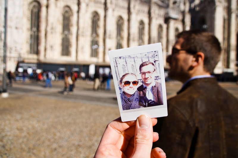Cropped Hand Of Woman Holding Photograph Against Milan Cathedral