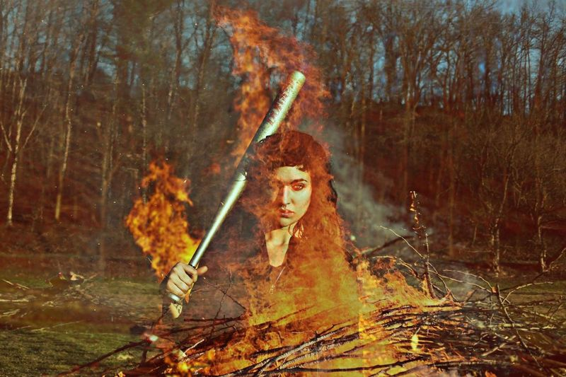 Double exposure of woman carrying baseball bat and fire burning in forest