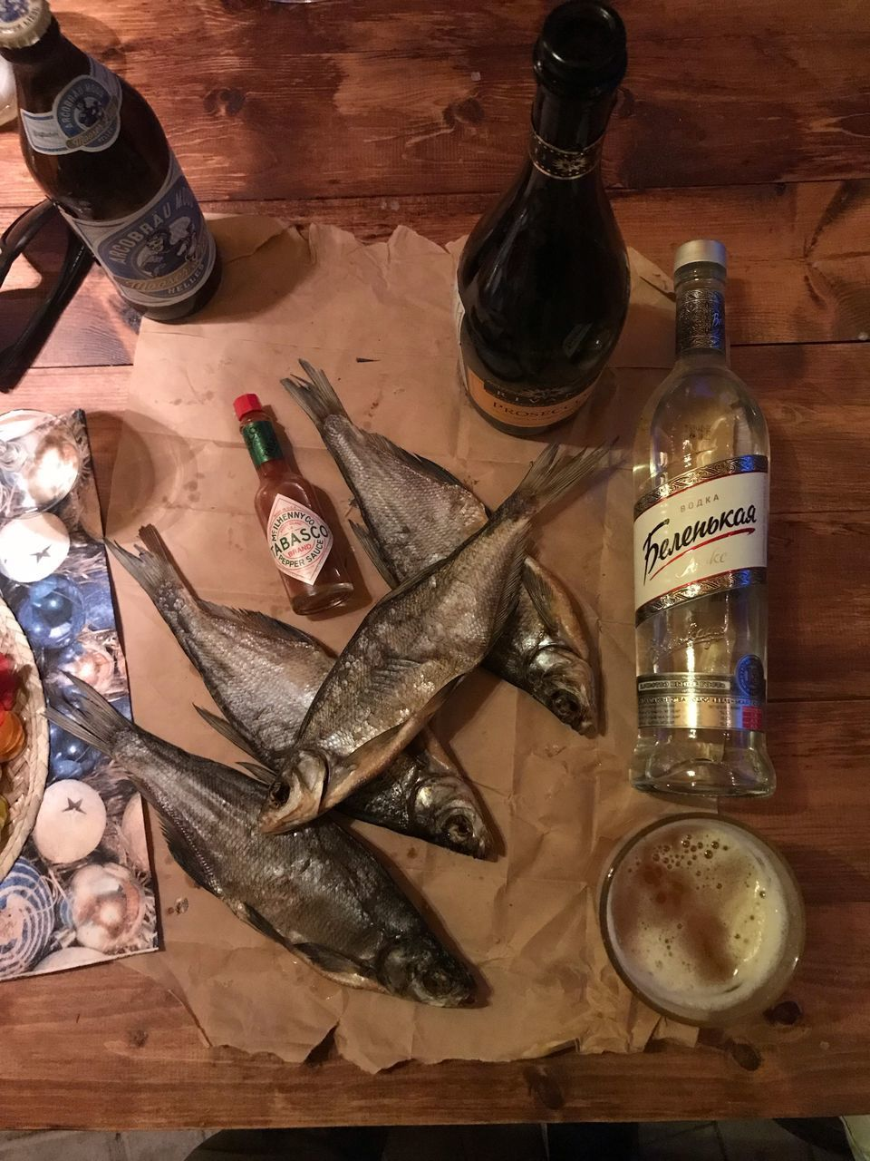 bottle, food and drink, container, still life, food, indoors, table, seafood, high angle view, fish, no people, choice, glass - material, alcohol, wood - material, animal, label, vertebrate, freshness, wellbeing