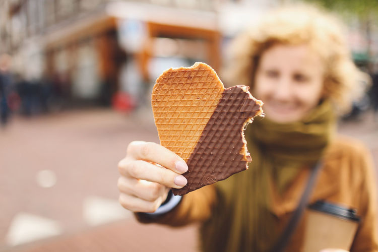 Young woman holding eaten heart shape waffle on walkway