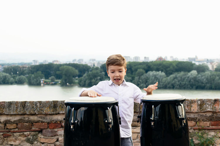 Boy playing bongo against clear sky