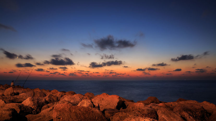 Rocks at sea against cloudy sky during sunset