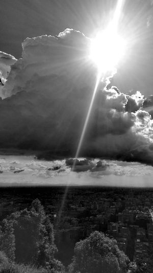 Sun shining over sea against sky