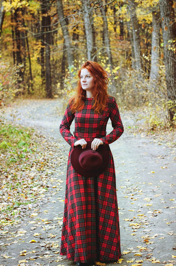 The red-haired girl in red dress walking in autumn park.
