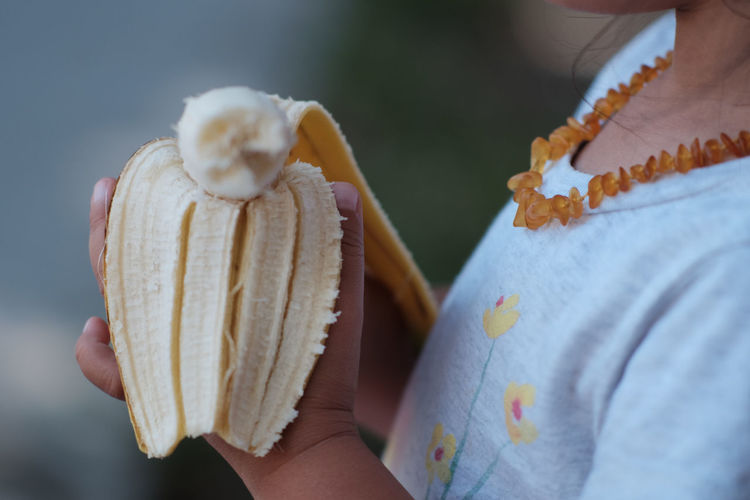 Close-up of child holding banana