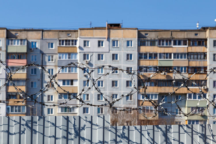 Residential multi-storey building behind a fence with barbed wire at daylight