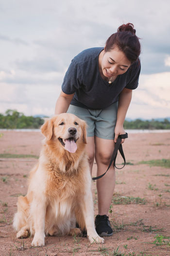 woman with her golden retriever dog playing outdoors. Dog Golden Retriever Pet Woman Beautiful Pets Happy People Cute Girl Park Young Outdoors Love Animal Grass Friend Portrait Nature Walking person Female Summer Lifestyle Outside White Smile Happiness Cheerful Owner Dogs Walk Friendly Fun Beauty Attractive Care Play Friendship Best  ASIA Thailand Domestic Domestic Animals Real People Day Land Young Adult Front View Women