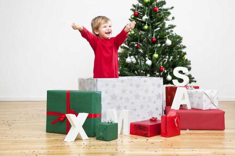 Full length of boy standing against christmas tree