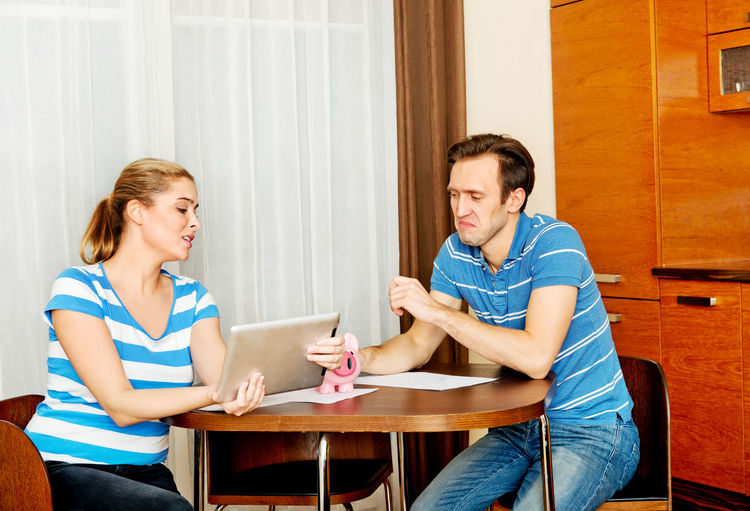 Couple discussing over digital tablet at home