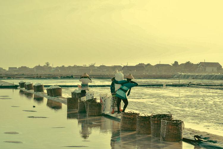 Rear view of people working at salt lake during sunset